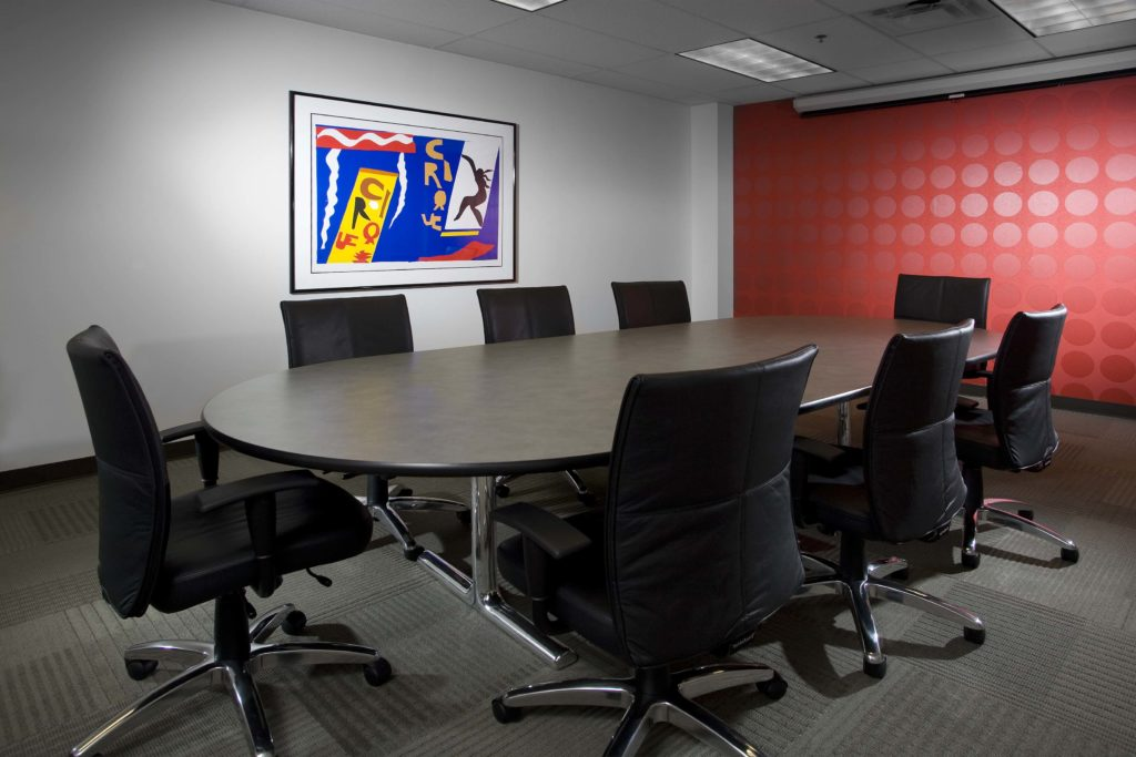 Conference room with black leather chairs and red polka dot wall
