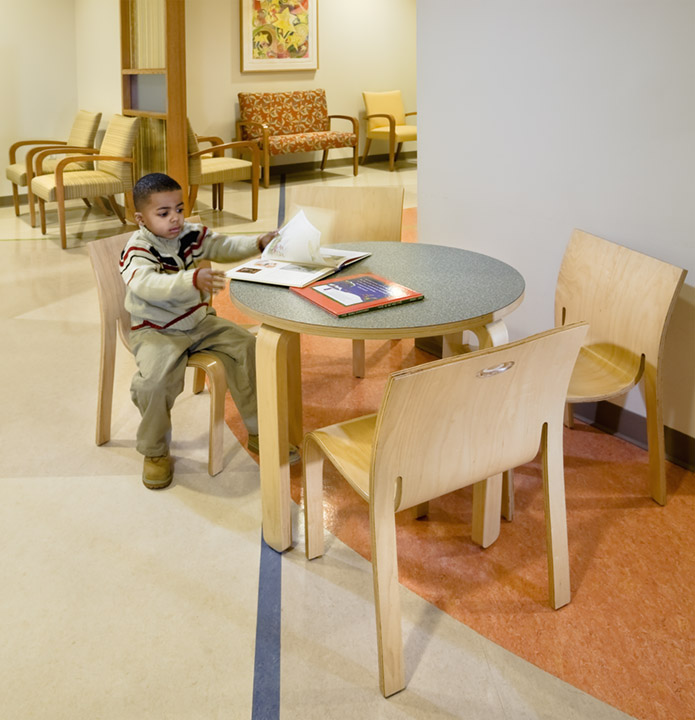 Little boy looks at books in hospital waiting room