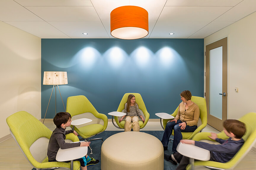 Woman and children talking in colorful modern chairs in counseling room