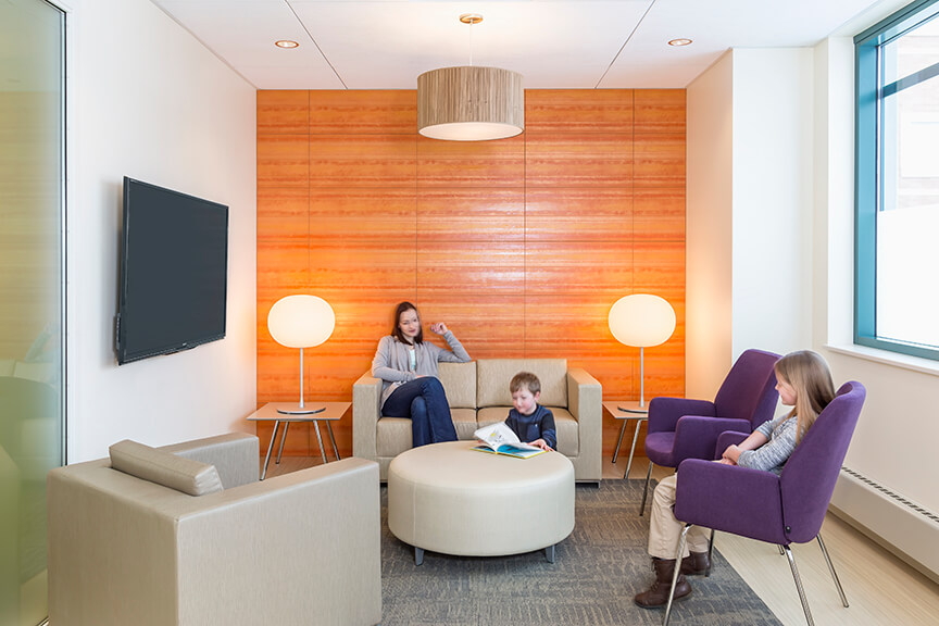 Family sitting in room with modern furniture and bright orange wall